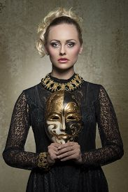 foto of gothic girl  - charming blonde girl posing in carnival shoot with antique baroque gothic costume black lace dress precious jewellery and theatrical mask in the hands - JPG