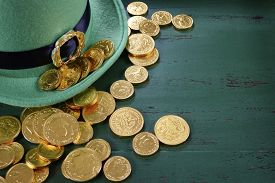 stock photo of shamrocks  - Happy St Patricks Day leprechaun hat with gold chocolate coins on vintage style green wood background with copy space. .