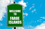 stock photo of faro  - Green road sign with greeting message WELCOME TO FAROE ISLANDS isolated over clear blue sky background with available copy space - JPG