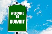 pic of kuwait  - Green road sign with greeting message WELCOME TO KUWAIT isolated over clear blue sky background with available copy space - JPG