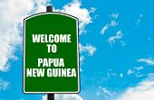 image of papua new guinea  - Green road sign with greeting message WELCOME TO PAPUA NEW GUINEA isolated over clear blue sky background with available copy space - JPG