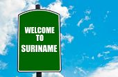 stock photo of suriname  - Green road sign with greeting message WELCOME TO SURINAME isolated over clear blue sky background with available copy space - JPG