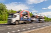 picture of car carrier  - car atomos traveling on a road blue sky clouds - JPG