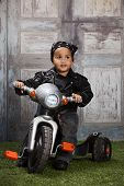 stock photo of tricycle  - Adorable mixed race toddler wearing a bandanna and leather jacket and riding a toy tricycle - JPG