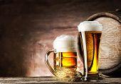 stock photo of beer mug  - Mug and a glass of light beer on background of old barrels - JPG