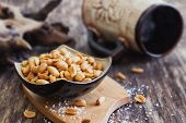 stock photo of salt-bowl  - salted peanut nuts in a bowl on the old wooden background - JPG