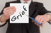 pic of grief  - Grief man in suit cutting text on paper with scissors - JPG