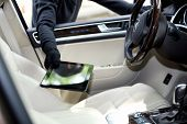 stock photo of stealing  - Man burglar steals the tablet of car - JPG