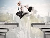 picture of gap  - Energetic business man jumping over a bridge with gap concept - JPG