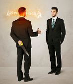 foto of backstabbers  - Angry businessman hiding a weapon behind his back  - JPG