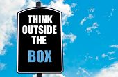 picture of thinking outside box  - THINK OUTSIDE THE BOX written on road sign isolated over clear blue sky background with available copy space - JPG