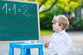 Little Boy At Blackboard Learning To Write poster