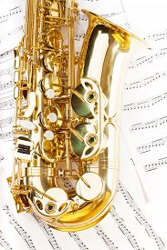 stock photo of musical scale  - View of shiny golden alto saxophone bow part on the musical notes background with standard scales exercises - JPG