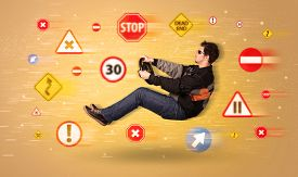 foto of slippery-roads  - Young driver with road signs around him concept - JPG