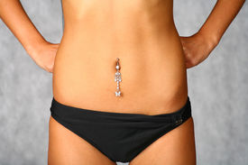 stock photo of pierced belly button  - belly with piercing of the slim girl in black underwear on the gray background - JPG