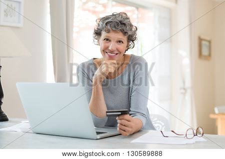 Happy senior woman making online payments of bill using laptop. Smiling mature woman shopping online