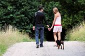 picture of walking away  - Young couple in meadow walking with dog - JPG