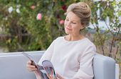 Senior woman reading a magazine sitting on a couch outdoor. Happy elderly woman reading a gossip mag poster