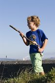 picture of emplacements  - a boy plays beside an old concrete bunker with a stick for a gun - JPG