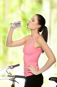 picture of drinking water  - Attractive brunette woman with bike in forest drinking water - JPG