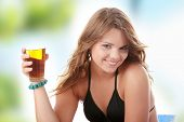 Young woman in bikini drinking ice tea isolated