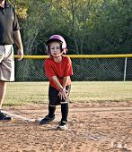 pic of little-league  - A young girl on base with her coach watching after making a hit during a little league softball game - JPG