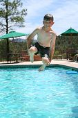 Young Boy Smiling And Jumping Into A Swimming Pool