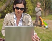 Attractive young mother is sitting on the ground in the garden and using a laptop while a 5 years ol