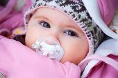 stock photo of teats  - A few months old baby outdoor in warm clothes in a cold winter day - JPG