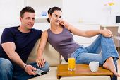 Happy young couple sitting on sofa at home, watching TV.
