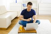 Casual young man using laptop computer at home, sitting at floor, holding pear in hand.