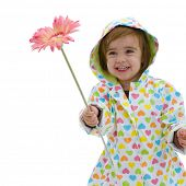 Happy small girl wearing raincoat and boots, holding pink flower, laughing. Isolated on white background.