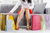 Young woman sitting on couch after day of shopping, packing colorful shopping bags.