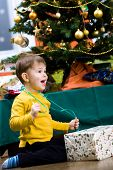 picture of merry chrismas  - Happy little boy opening Chrismas present at Christmas Eve under the Christmas tree - JPG