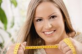 Happy young woman on diet holding tape measure, smiling.