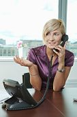 stock photo of people talking phone  - Happy young businesswoman sitting at table in office meeting room - JPG