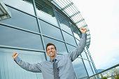Happy successful businessman raising arms outdoor, smiling.