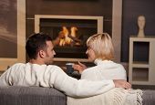 Young romantic couple sitting on sofa in front of fireplace at home, looking at each other, talking,