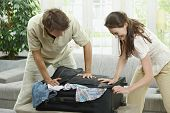 Couple packing for holiday, trying to close suitcase full with clothes.