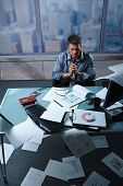 Tired businessman calling from office papers lying all around, picture taken from high angle.