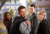 Portrait of happy business team standing outdoor having fun, sticing out their tongues.