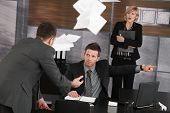 Angry boss firing employee, showing door. Papers flying in air, scared secretary standing in backgro