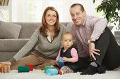 picture of nuclear family  - Happy family sitting on floor smiling at camera with baby girl - JPG