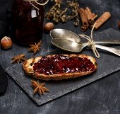 Toast With Raspberry Jam, Two Iron Spoons And A Jar Of Jam On A Black Background poster