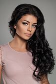 Brunette Beauty. Beautiful Brunette Woman With Makeup And Long Permed Hairstyle. Tanned Skin, Pink L poster
