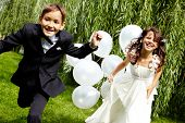 stock photo of fiance  - Portrait of laughing children bride and groom with balloons running in park - JPG