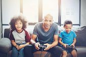 African American Family At Home Sitting In Sofa Couch And Playing Console Video Games Together. poster