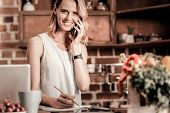Постер, плакат: Phone Call Delighted Positive Cheerful Woman Holing Her Phone And Making A Phone Call While Being R