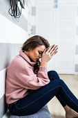 Young Woman After Cry Sitting On Whte Floor At Home In Depression. A Woman Sitting Alone And Depress poster