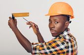 African American Worker Builder Uses Building Ruler And Looks At Camera poster